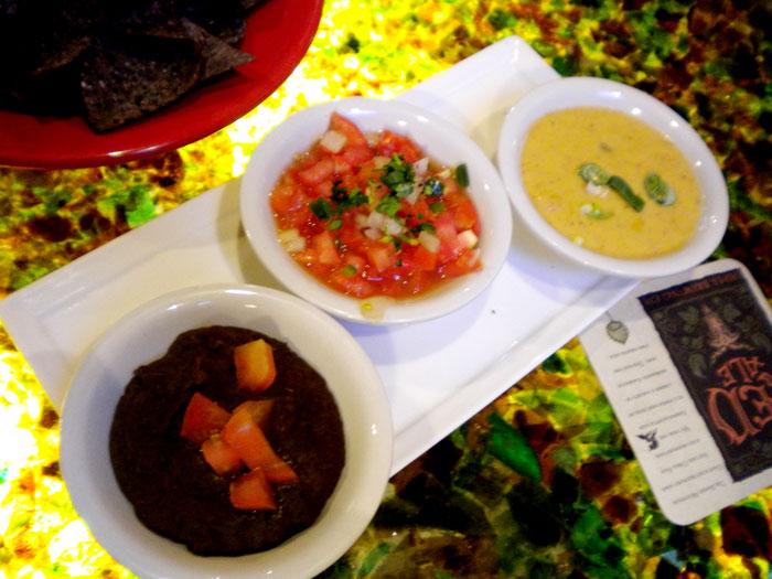Tortilla chips with bean dip, salsa, and warm cheese dip