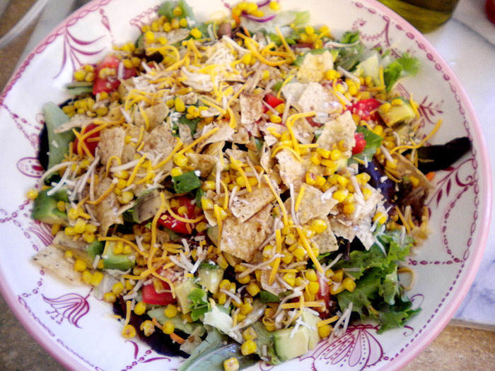 Mixed greens with black beans, roasted corn, tomatoes, tortilla chips, cheddar cheese, and red wine vinagrette