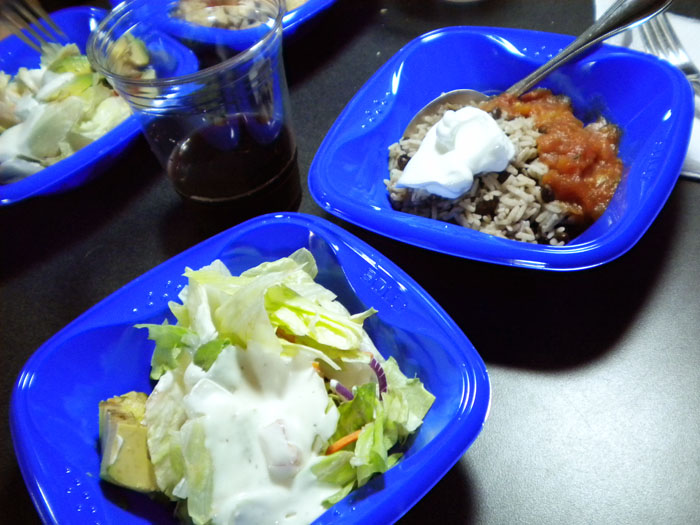 An RV meal of black beans with salsa, rice, and salad.