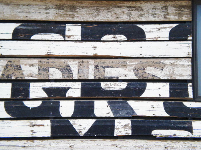 I guess this was once a sign, reused as siding. Cool!