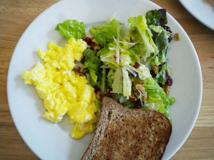 Scrambled eggs with salad and toast.