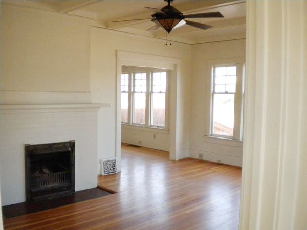 The livingroom has lots of windows, a fireplace, a built-in bookcase, and a new ceiling fan.