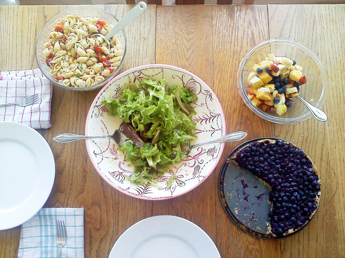 Green salad with vinagrette, pasta salad with tomatoes, corn, basil, and lemon vinagrette, fruit salad, and blueberry tart.