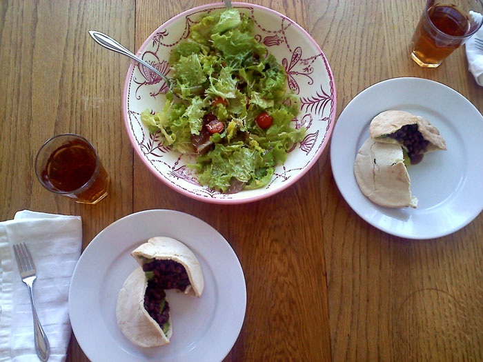 Green salad with tomatoes and parmesan, pita sandwiches with black beans, cream cheese, and avocado.