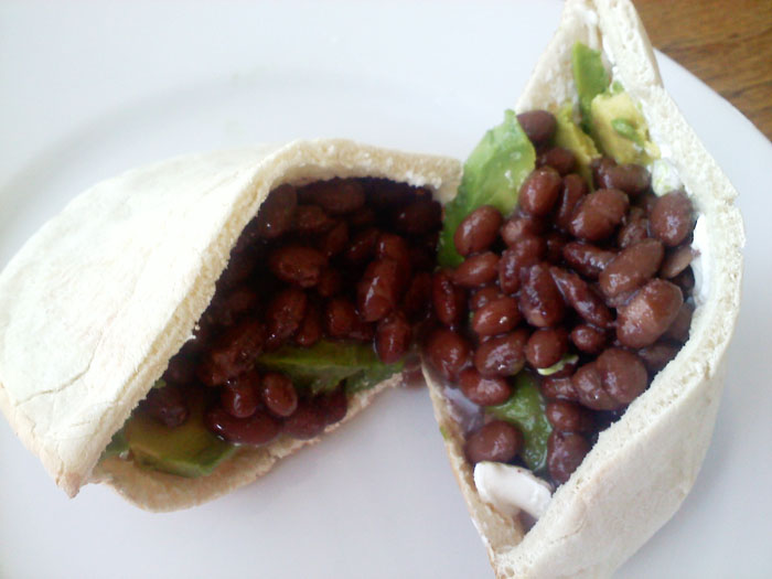 Pita sandwiches with black beans, cream cheese, and avocado.