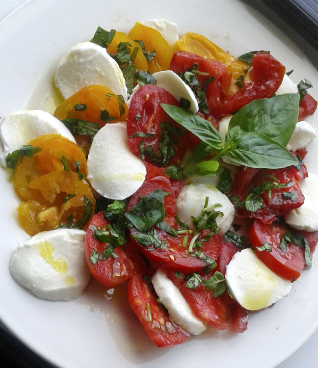 Caprese salad with farmers market tomatoes, basil, olive oil, and fresh mozerella.