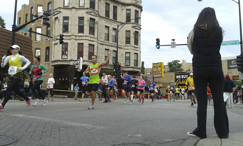 Runners wave to the spectators on Clark St. in Lincoln Park, Chicago Marathon